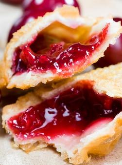 Mermelada de cereza que fluye real en un bollo crujiente, se encuentra junto con bayas de cereza rojas maduras, comida lista para comer