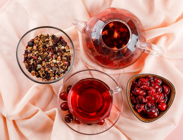 Mermelada de cerezas en un tazón con cerezas, té, hierbas secas en rosa y textil