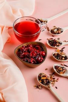 Mermelada de cerezas en un tazón con hierbas secas, té de ángulo alto en textil y rosa