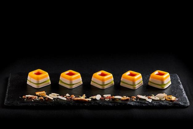 Mermelada de color, dispuesta en una hermosa línea en un plato negro. fondo de comida. concepto de comida fusión, bajo perfil, copia espacio.