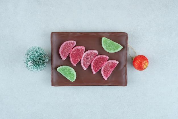Mermelada dulce con bola de navidad y árbol en plato oscuro.