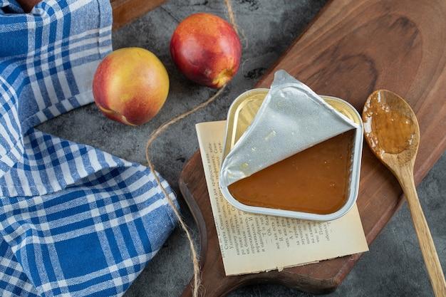 Mermelada dulce con melocotones y cuchara de madera sobre plancha de madera