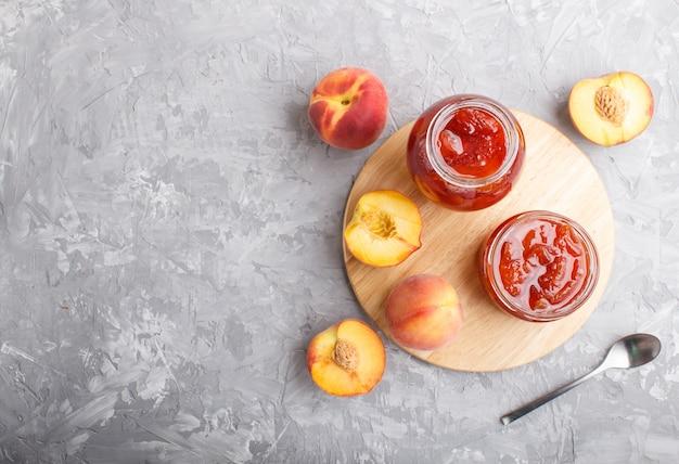 Mermelada de durazno en un frasco de vidrio con frutas frescas sobre fondo de hormigón gris