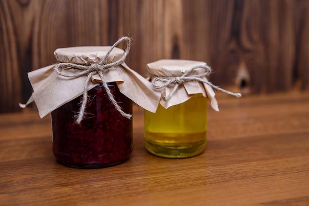 Mermelada de frambuesa y miel en frascos de vidrio sobre madera
