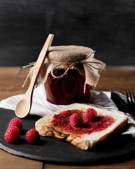 Mermelada de frambuesa sobre pan con frasco y cuchara