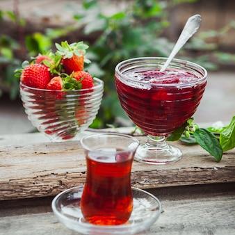 Mermelada de fresa en un plato con cuchara, té en vidrio, fresas, planta de primer plano en la mesa de madera y jardín
