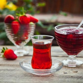 Mermelada de fresa en un plato con un vaso de té, cuchara, fresas, vista lateral en la mesa de madera y patio