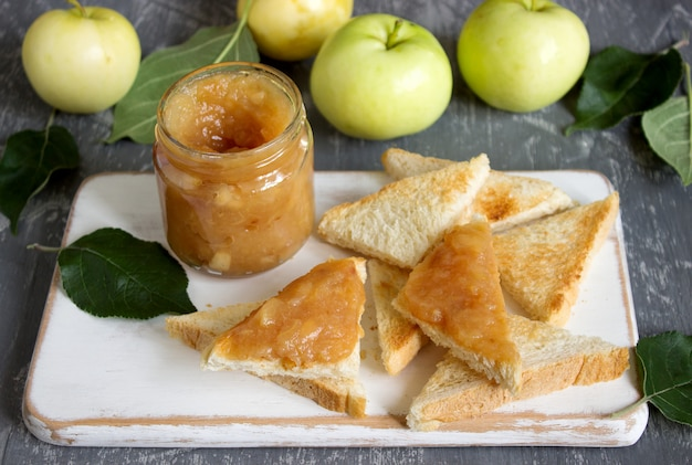 Mermelada de manzana en un frasco de vidrio con tostadas de pan y manzanas maduras sobre una superficie de madera. estilo rústico