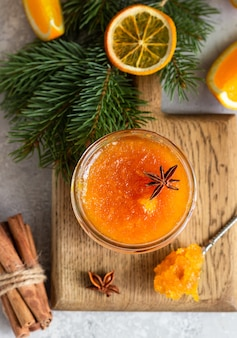 Mermelada de naranja en un frasco de vidrio con especias de invierno y ramas de abeto.