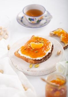 Mermelada de naranja o mandarina sobre un fondo blanco.