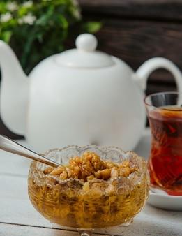 Mermelada de nuez azerbaiyana sin piel, servida con té negro en vidrio armudu