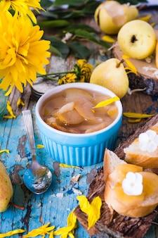 Mermelada de peras en un recipiente sobre una mesa de madera