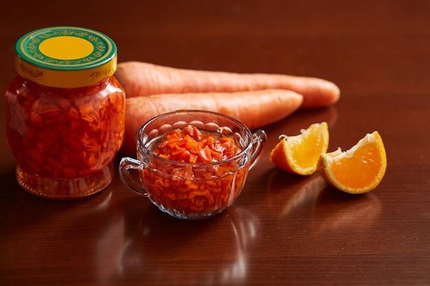 Mermelada de zanahoria en un frasco y un tazón, zanahorias, rodajas de mandarina para la decoración.