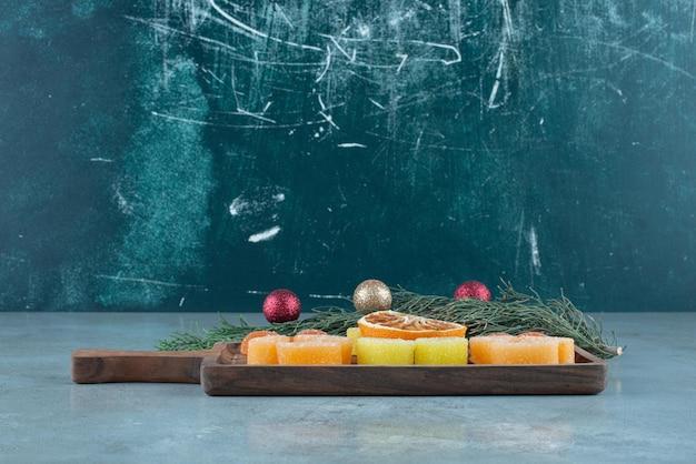 Mermeladas y una rodaja de naranja seca en una bandeja junto a una pequeña guirnalda sobre mármol.
