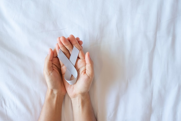 Mes de concientización sobre el cáncer de cerebro, mano de mujer sosteniendo una cinta de color gris para apoyar a las personas que viven. concepto de salud y día mundial contra el cáncer
