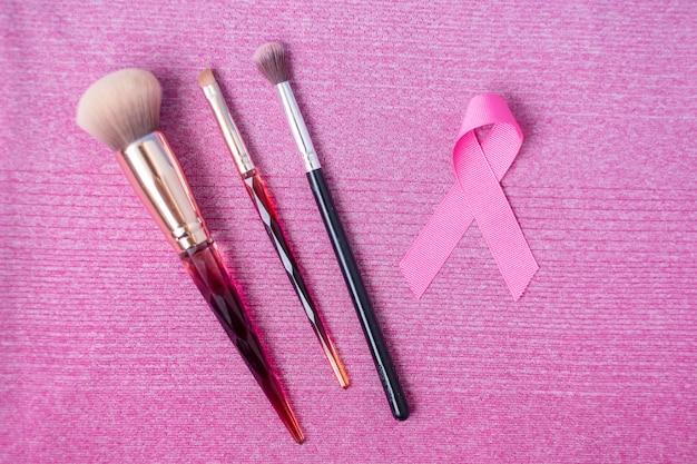 Mes de concientización sobre el cáncer de mama con cinta rosa y pinceles de maquillaje