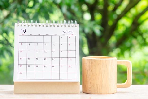 Mes de octubre, escritorio de calendario 2021 para organizador de planificación y recordatorio en mesa de madera con fondo de naturaleza verde.