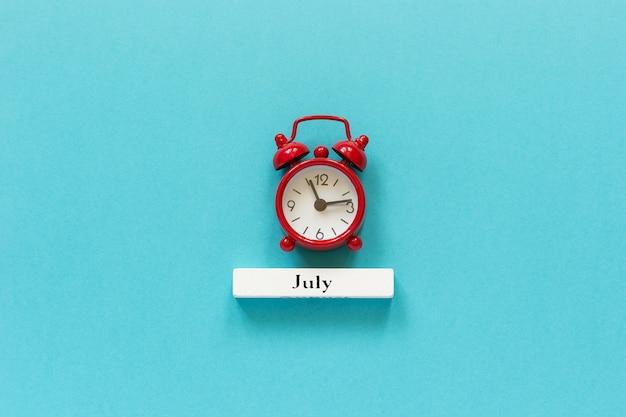 Mes de verano del calendario de madera julio y despertador rojo en fondo del papel azul.