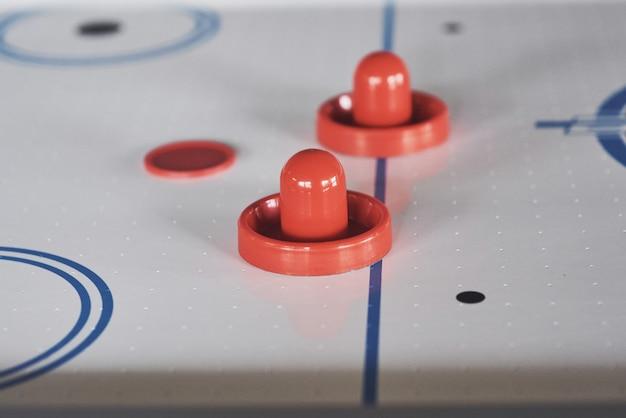 Mesa de air hockey con iluminación de ventana y palo de hockey de juguete rojo