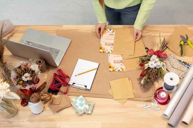Mesa alta vista de flores y elementos de papelería
