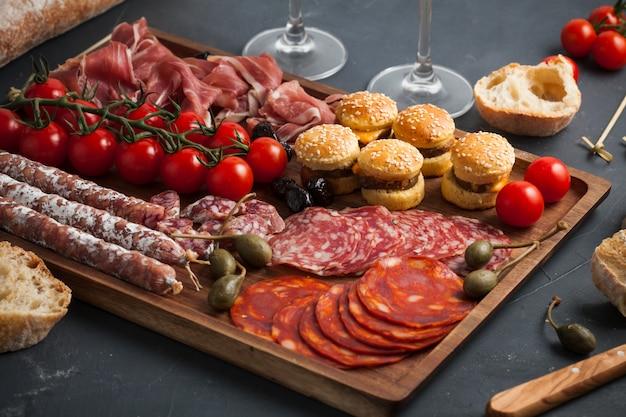 Mesa de aperitivos con diferentes antipasti, queso, embutidos, snacks y vino.
