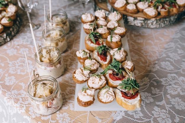 Mesa de banquete de catering bellamente decorada con diferentes bocadillos y aperitivos en el evento corporativo de la fiesta de cumpleaños de navidad o la celebración de la boda