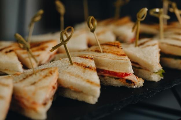 Mesa de banquete de catering bellamente decorada con diferentes bocadillos y aperitivos con sándwich