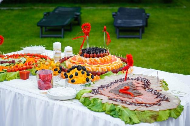 Mesa de banquete decorada con corazones de fruta y chorizo.