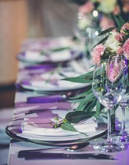 Mesa para banquetes con cubiertos y flores.