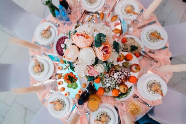 Mesa bellamente decorada en restaurante con diferentes comidas para la cena.