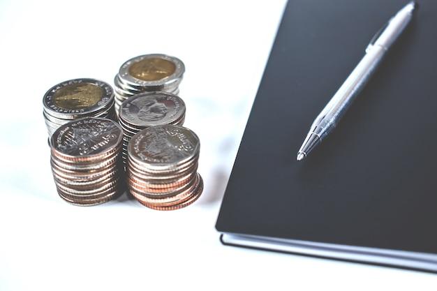 En la mesa blanca hay cuadernos, bolígrafos y montones de monedas de ahorrar dinero.