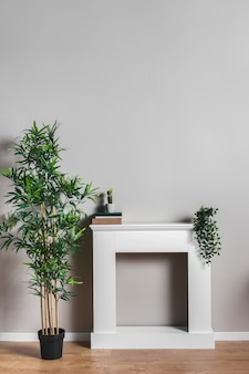 Mesa blanca con libros y plantas.