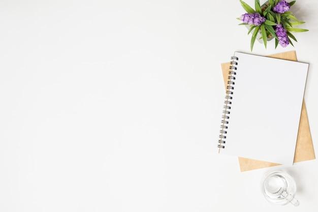 Mesa blanca mínima para escritorio de oficina con cuadernos, vaso de agua potable y maceta.