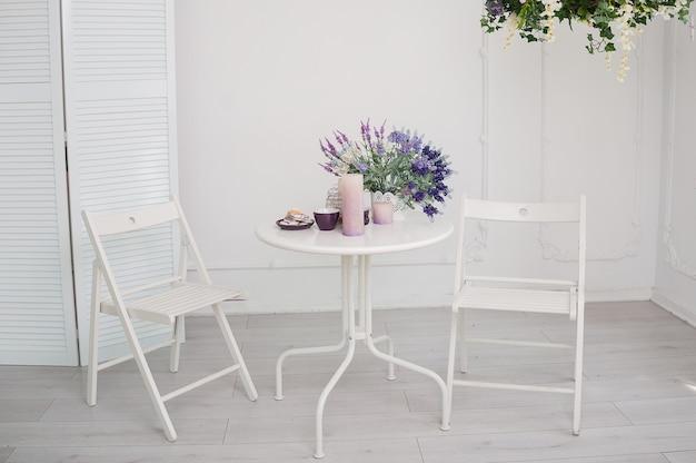 Mesa blanca con un ramo de flores y dos sillas en la sala.