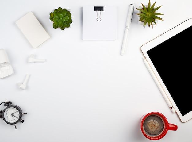 Mesa blanca con tableta electrónica, tarjetas en blanco