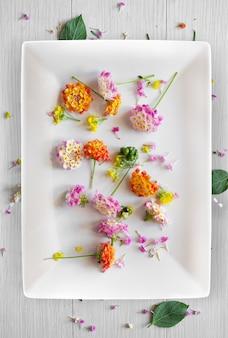 Mesa blanca con tenedor, plato y pequeñas flores utilizables como fondo