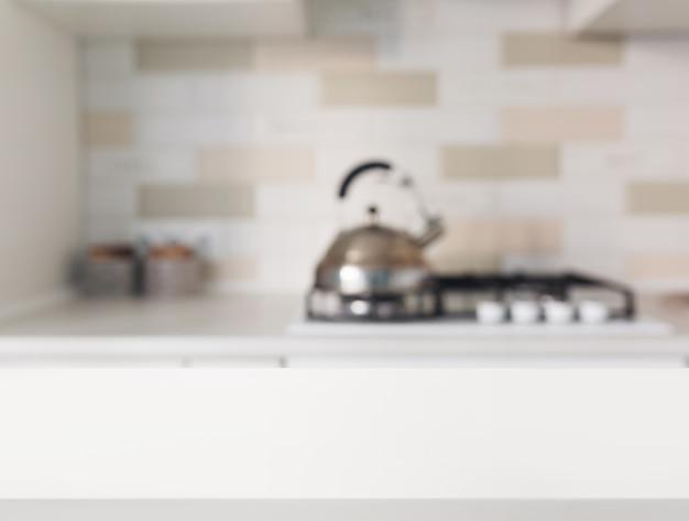 Mesa blanca vacía frente a mostrador de cocina borrosa