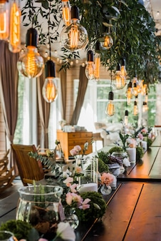 Mesa de boda festiva con bulbos de guirnalda de edison colgando de cordones, decorada con ramas de flores verdes. efecto granulado
