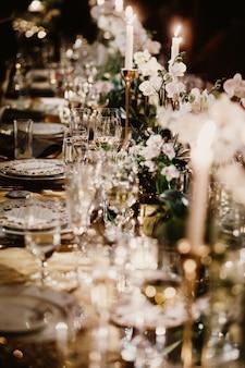 Mesa de boda con velas decoradas con ramos de flores.