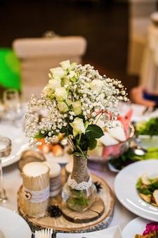 Mesa de bodas en el restaurante decorada con flores en estilo rústico.