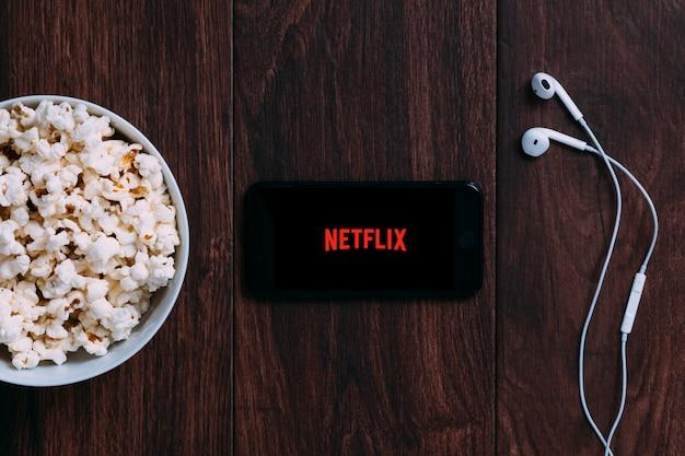 Mesa con botella de palomitas de maíz y logotipo de netflix en apple iphone y auriculares.