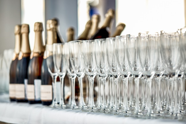 Mesa buffet con copas de champaña y botellas de champaña.