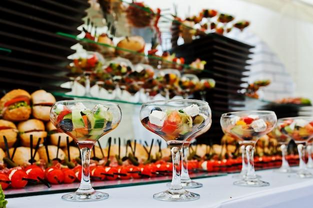 Mesa buffet de recepción con hamburguesas, bocadillos fríos, carnes y ensaladas.