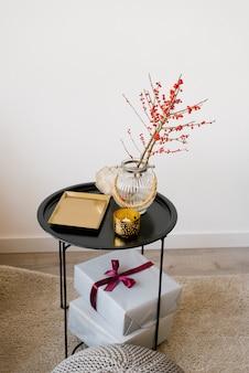Una mesa de café con una bandeja de oro, ramas con frutos rojos en un jarrón de vidrio y cajas de regalo con cintas y un lazo.