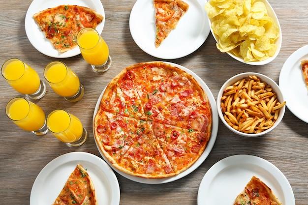 Mesa en casa con pizza y bebidas para amigos.