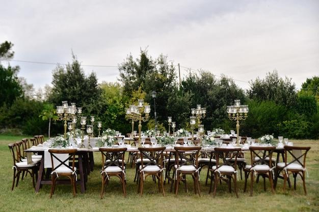Mesa de celebración de bodas decorada con asientos para invitados al aire libre en los jardines