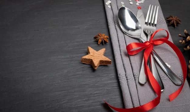 Mesa de cena de navidad con cubiertos, servilleta gris y vista superior de especias de invierno.