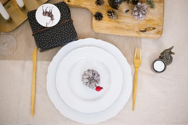 La mesa de la cena de navidad se sirve con un plato vacío con tenedor y cuchillo.