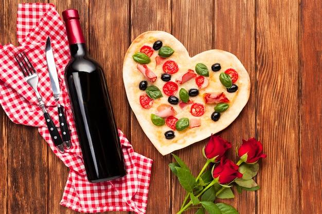 Mesa de la cena romántica plana con botella de vino.