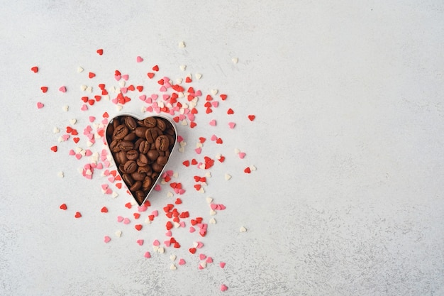 Mesa de cocina con cortadores de galletas y granos de café, espolvorear azúcar rosa sobre graytable. concepto de horneado dulce para el día de san valentín. endecha plana, vista superior,